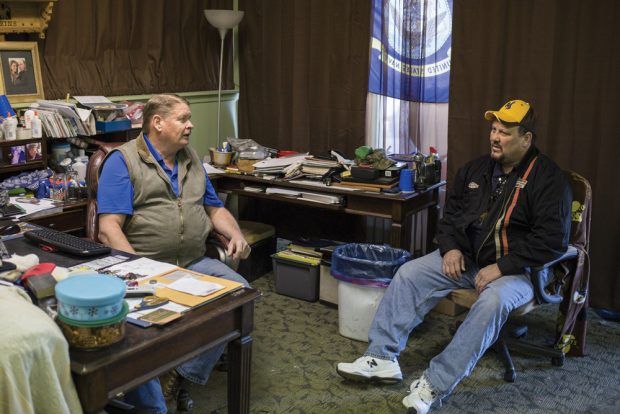 Mark Perkins, left, and Scott Pearce talk about recent layoffs from the nearby Black Thunder Coal Mine at Perkins' electrical shop in Wright, Wyo., on April 5, 2016. Perkins is closing his business after the mine laid off hundreds of workers, including Pearce, due to a dramatic decline in demand for coal. The town, with a population of less than 2,000, relies heavily on the energy industry to sustain itself. As energy prices and demand for coal decline the state is struggling to support it's ailing, energy-dependent economy.