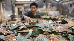 A worker sorts through stripped computer boards in Guiyu, China. Photo credit: Fortune.com
